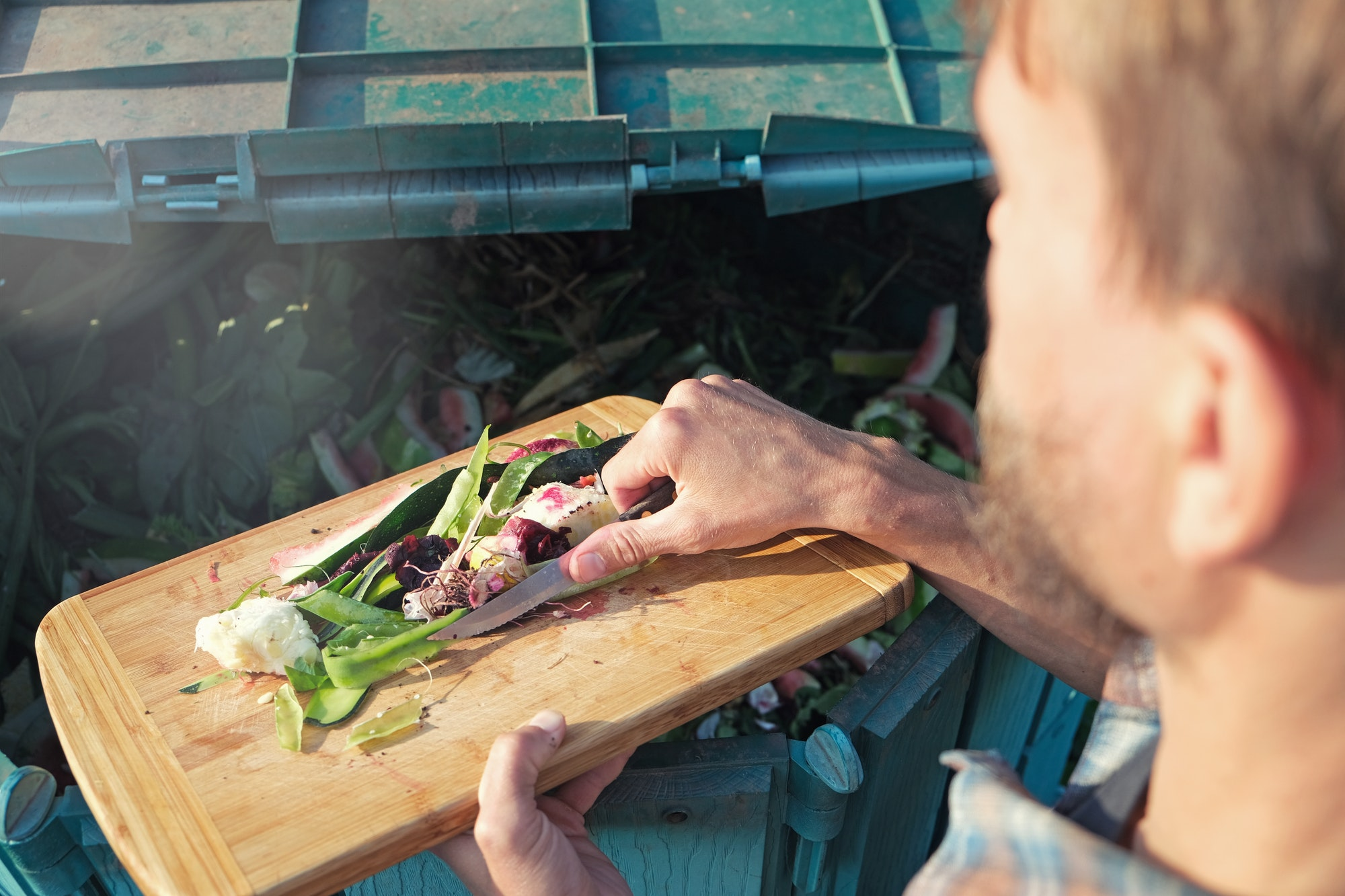 Person throws kitchen food waste into compost heap to make organic fertilizer. Composting.